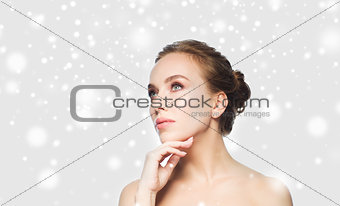 beautiful young woman touching her face over snow