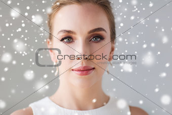 close up of beautiful woman or bride over snow