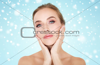 beautiful woman touching her face over snow