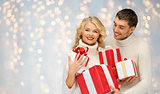smiling man and woman with presents over lights