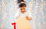 smiling little girl opening gift box over lights
