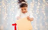 smiling little girl opening gift box over lights
