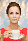 woman in red with cup of coffee over lights