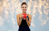 smiling woman holding red gift box over lights