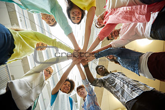 group of international students with hands on top