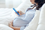 close up of pregnant woman with smartphone in bed