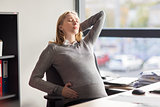 tired pregnant businesswoman at office work