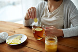 close up of woman adding ginger to tea with lemon