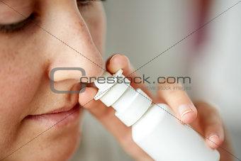 close up of sick woman using nasal spray