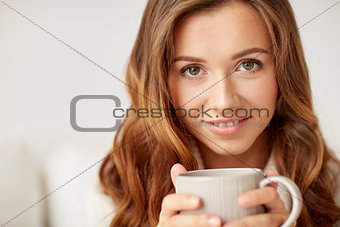 close up of happy woman with coffee cup at home