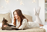happy young woman with cat lying in bed at home
