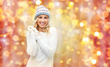 smiling young woman in winter hat and sweater