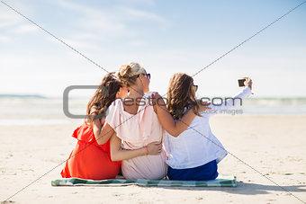 happy women taking selfie by smartphone on beach