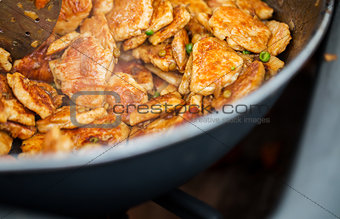 close up of meat in wok pan at street market