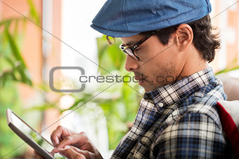 close up of man with tablet pc sitting at cafe