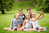 happy kids or friends taking selfie in summer park