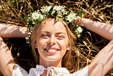 happy woman in wreath of flowers lying on straw