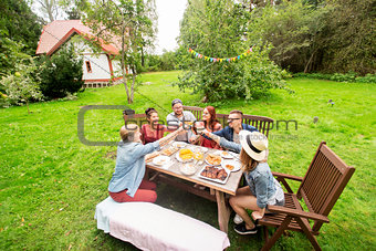 happy friends having dinner at summer garden party