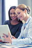 smiling businesswomen with tablet pc in office