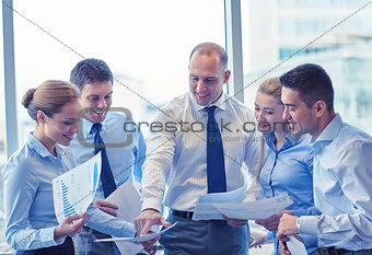 business people with papers talking in office