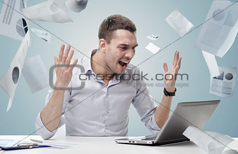 angry businessman with laptop and papers shouting