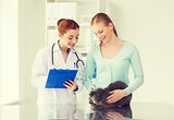happy woman with cat and doctor at vet clinic