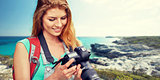 happy woman with backpack and camera over seashore