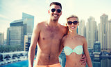 happy couple in swimwear over dubai city waterside