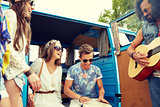 happy hippie friends playing music over minivan