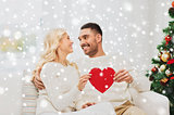 happy couple with red heart at home for christmas