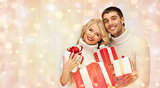 happy couple in sweaters holding christmas gifts