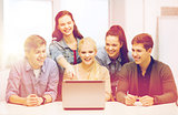 smiling students looking at laptop at school