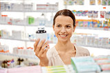 happy female customer with drug jar at pharmacy
