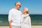 happy senior couple hugging on summer beach