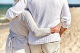 close up of happy senior couple hugging on beach