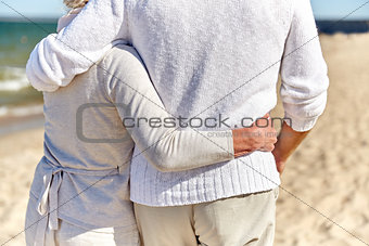 close up of happy senior couple hugging on beach