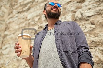 close up of man with paper coffee cup on street
