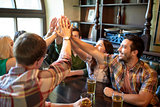 friends with beer making high five at bar or pub