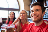 fans or friends watching football at sport bar