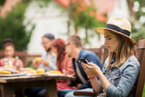 woman with smartphone and friends at summer party