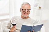 happy senior man drinking wine and reading book