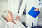 doctor visiting happy senior woman at hospital