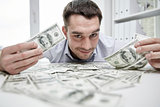 happy businessman with heap of money in office