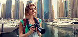 woman with backpack and camera over dubai city