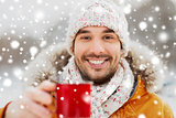 happy man with tea cup outdoors in winter