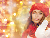 happy woman in hat, scarf and pullover over lights