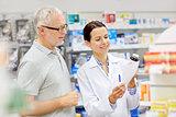 pharmacist and senior man buying drug at pharmacy