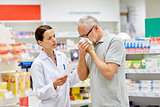 pharmacist and senior man with flu at pharmacy
