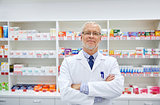 senior male pharmacist in white coat at drugstore