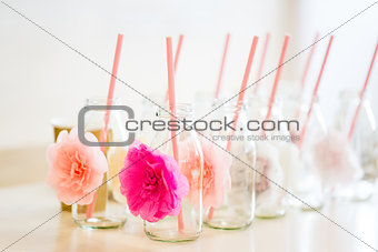 close up of glass bottles for drinks with straws